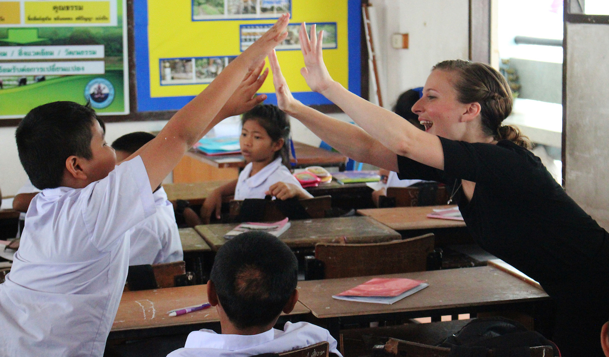 Hannah high-fiving a student at English camp.