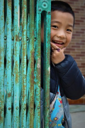 A boy peeks around a fence. Teach in Vietnam