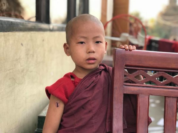 A boy monk poses for a photograph. Come teach monks in Myanmar!