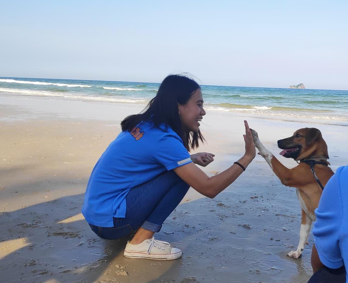 Rescue Paws volunteer holding dog on the beach in Hua Hin, Thailand